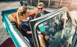 Giovani e coppie attraenti che si siedono in una retro automobile lussuosa Immagine Stock Libera da Diritti