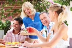 Giovani e coppie maggiori che godono del pasto della famiglia Fotografia Stock