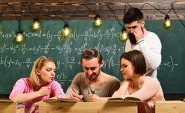 Giovani e donne che si siedono nell'istituto universitario Studenti che usando tecnologia per imparare le lezioni del gruppo di s immagine stock