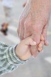 Giovani e mani anziane, esterne immagini stock