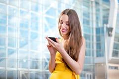 Giovani e sms di battitura a macchina sorridenti della donna sul telefono davanti al livello Immagine Stock