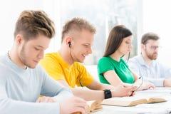 Giovani e studenti astuti che imparano in un'aula Immagine Stock