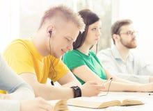 Giovani e studenti astuti che imparano in un'aula Fotografie Stock Libere da Diritti