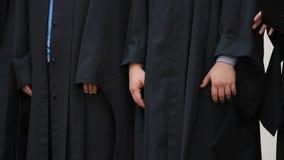 Giovani emozionanti in abiti accademici che lasciano fase dopo la ricezione dei diplomi archivi video