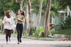 Giovani esercizio e riscaldamento asiatici felici della donna fotografia stock