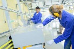 Giovani esperti di metallurgia sul lavoro nell'officina della scuola immagini stock