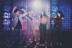 Giovani felici che ballano nel night-club fotografie stock