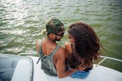 Giovani felici che si siedono e che abbracciano sulla barca Immagini Stock Libere da Diritti
