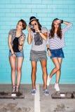 Giovani felici con la macchina fotografica della foto divertendosi davanti al blu Immagine Stock