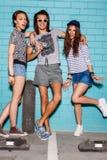 Giovani felici con la macchina fotografica della foto divertendosi davanti al blu Fotografia Stock