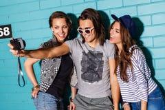 Giovani felici con la macchina fotografica della foto divertendosi davanti al blu Fotografia Stock Libera da Diritti