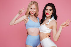 Giovani felici due donne vestite in swimwear Fotografia Stock