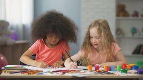 Giovani femmine multirazziali che si siedono alla tavola e che disegnano con le matite variopinte stock footage