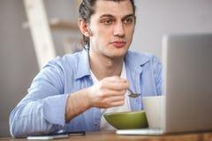 Giovani fiocchi di mais mangiatori di uomini con latte ed e guardando allo schermo del computer portatile Immagini Stock