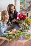 Giovani fioristi multietnici che lavorano con la compressa digitale ed i fiori nel negozio di fiore Immagini Stock Libere da Diritti