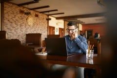 Giovani free lance che lavorano con il computer portatile e che parlano sul cellulare con il cliente in caffè Uomo d'affari cauca fotografia stock libera da diritti