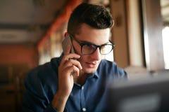 Giovani free lance che lavorano con il computer portatile e che parlano sul cellulare con il cliente in ufficio Uomo d'affari cau fotografie stock