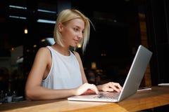Giovani free lance femminili affascinanti che per mezzo del computer portatile per il lavoro di distanza mentre sedendosi nell'in Fotografia Stock Libera da Diritti