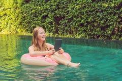 Giovani free lance femminili che si siedono vicino allo stagno con il suo computer portatile nell'hotel che passa in rassegna in  fotografia stock