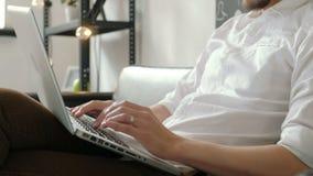 Giovani free lance maschii che lavorano dalla casa tramite computer portatile, tipo dei pantaloni a vita bassa che per mezzo del  stock footage