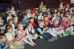 Giovani frequentatori di teatro bambini che guardano entusiasta il teatro Smeshariki dello spettacolo di burattini del Natale dei Fotografie Stock Libere da Diritti