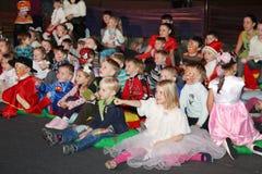 Giovani frequentatori di teatro bambini che guardano entusiasta il teatro Smeshariki dello spettacolo di burattini del Natale dei Immagini Stock Libere da Diritti