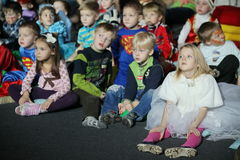 Giovani frequentatori di teatro bambini che guardano entusiasta il teatro Smeshariki dello spettacolo di burattini del Natale dei Immagini Stock