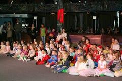 Giovani frequentatori di teatro bambini che guardano entusiasta il teatro Smeshariki dello spettacolo di burattini del Natale dei Immagine Stock Libera da Diritti