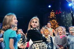 Giovani frequentatori di teatro bambini che guardano entusiasta il teatro Smeshariki dello spettacolo di burattini del Natale dei fotografia stock