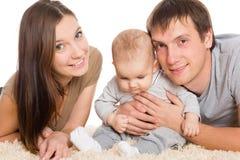 Giovani genitori allegri con la loro menzogne del figlio immagine stock