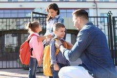 Giovani genitori che dicono arrivederci ai loro piccoli bambini fotografie stock