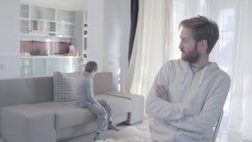 Giovani genitori che discutono e disperdere alle stanze differenti Il bambino è spaventato e in perdita Il marito si occupa irosa stock footage
