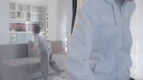 Giovani genitori che discutono e disperdere alle stanze differenti Il marito si occupa irosamente della moglie di partenza e giur archivi video