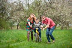 Giovani genitori che insegnano a suo figlio a guidare una bici fotografia stock