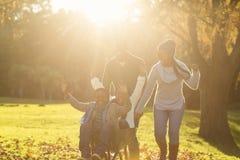 Giovani genitori che tengono i loro bambini in una carriola Fotografia Stock