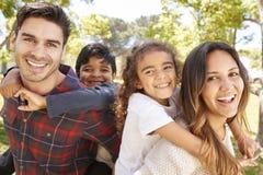 Giovani genitori che trasportano sulle spalle i loro due bambini all'aperto immagini stock