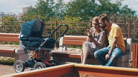 Giovani genitori con carrozzina sul banco Usando Smartphone famiglia playground video d archivio