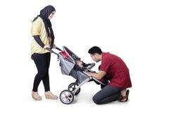 Giovani genitori con il bambino sul passeggiatore Fotografia Stock Libera da Diritti