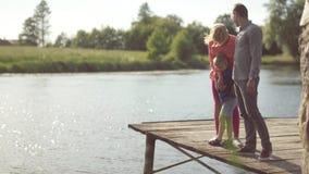 Giovani genitori con il loro figlio allo stagno stock footage