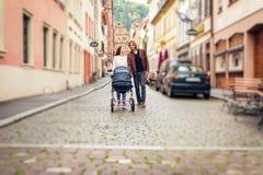 Giovani genitori con il passeggiatore di bambino nella città Immagine Stock