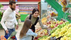 Giovani genitori con una piccola figlia scegliere le mele fresche in un grande supermercato stock footage