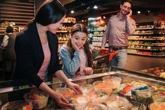 Giovani genitori e figlia in drogheria Scatola della tenuta della donna di insalata nelle mani e nel sorriso La ragazza sta oltre immagini stock