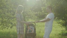 Giovani genitori felici con il bambino in trasporto nel parco famiglia playground Movimento lento 4k di giorno soleggiato di esta video d archivio