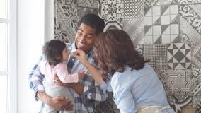 Giovani genitori multi-etnici che sorridono mentre spendendo tempo con il loro piccolo bambino dolce archivi video