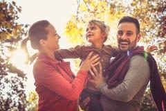 Giovani genitori sorridenti che camminano con la figlia fotografia stock