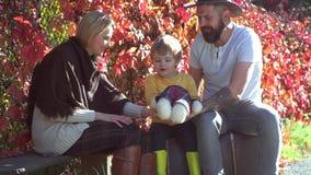 Giovani genitori sorridenti felici con poco figlio che risiede nelle foglie di autunno Famiglia di autunno Paternità della famigl stock footage