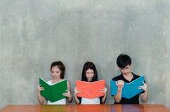 Giovani gruppo di studenti la scuola che leggente seria le cartelle prenotano immagini stock