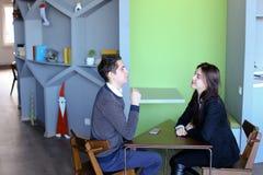 Giovani i colleghi femminili e maschii chiacchierano all'ora di pranzo e si siedono nel Ca Immagini Stock Libere da Diritti