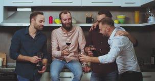 Giovani i tipi felici e carismatici a casa si divertono che beve insieme il vino e che ritiene grande, multi gruppo etnico video d archivio