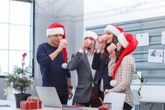Giovani impiegati di concetto alla società ed alla bevanda di Natale dai vetri di plastica una priorità bassa rossa immagini stock libere da diritti